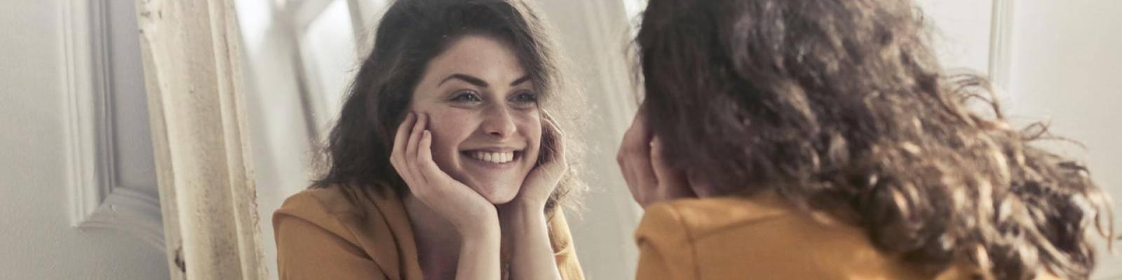 Vrouw kijkt blij in spiegel