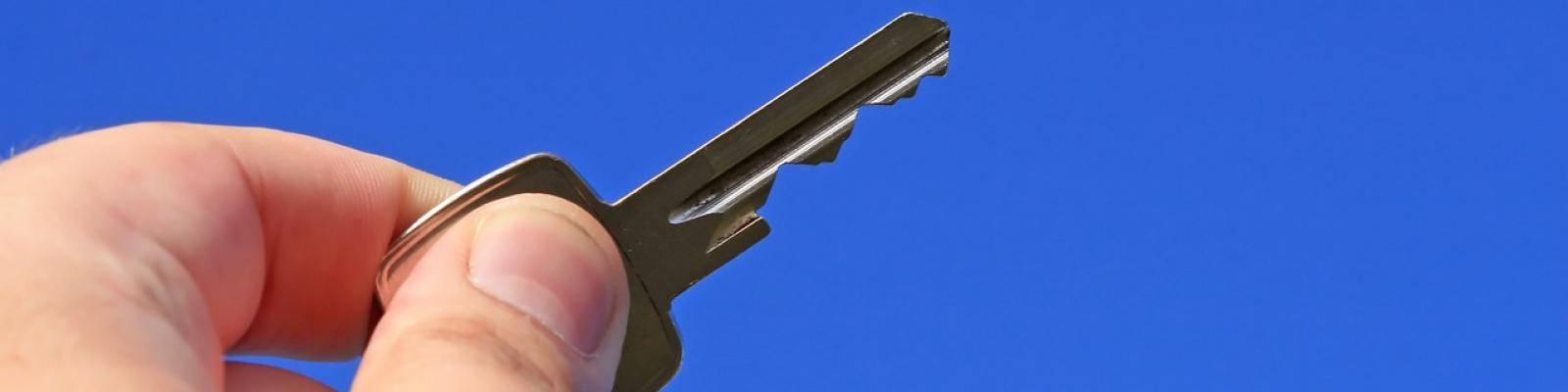 Hand met sleutel in lucht