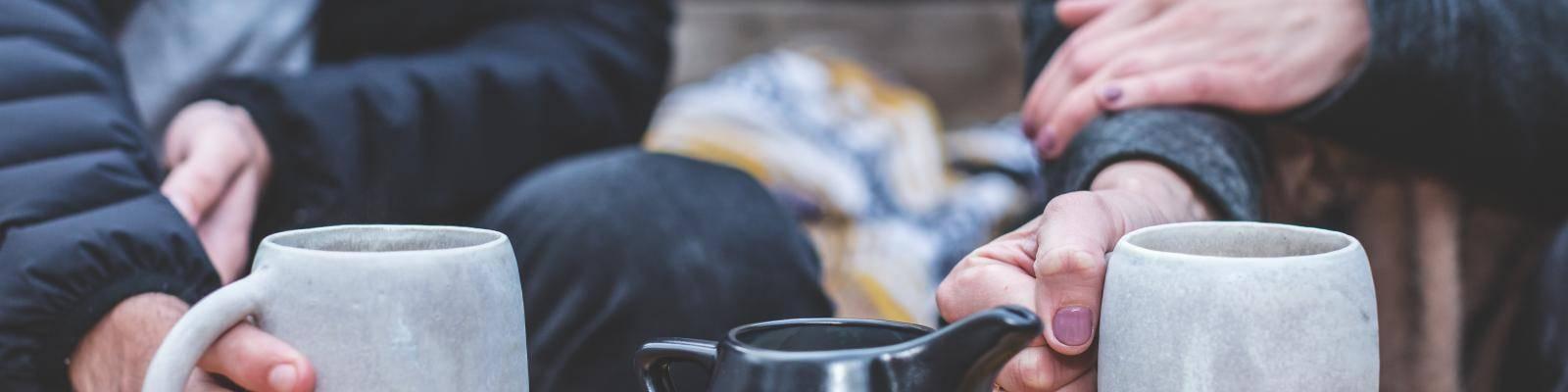 Handen om koffiemokken
