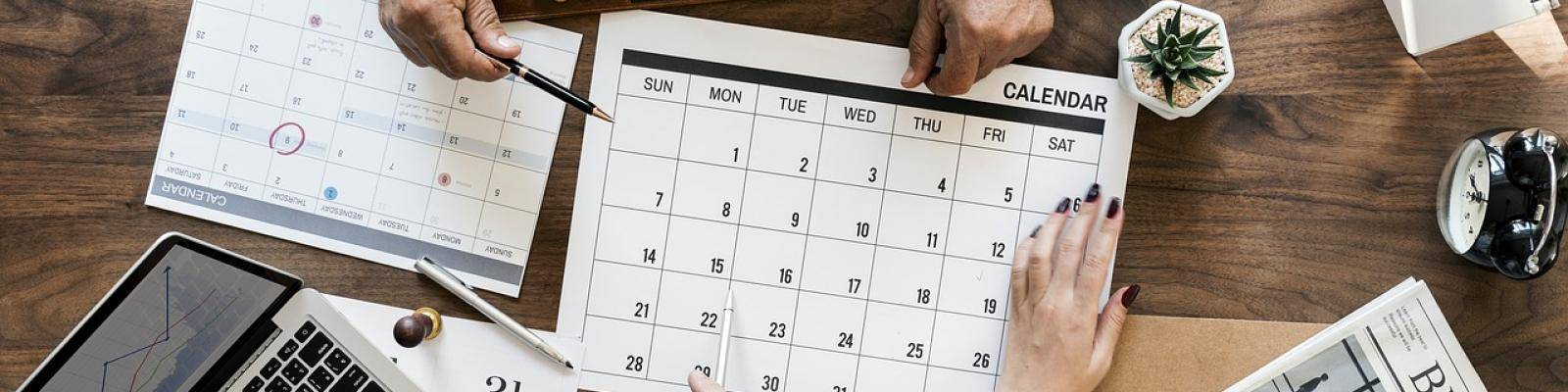 Mensen met kalenders op tafel