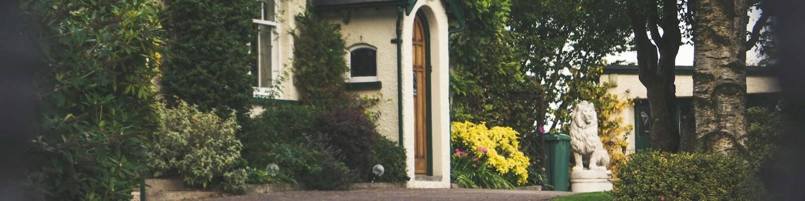 Huis met groene voortuin en standbeeld