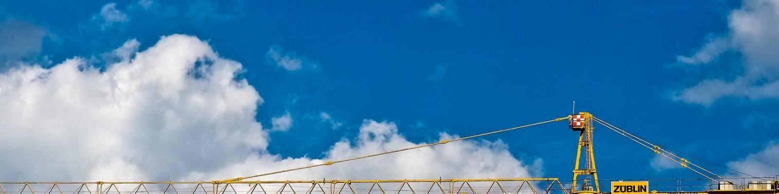 Hijskraan en blauwe lucht met wolken