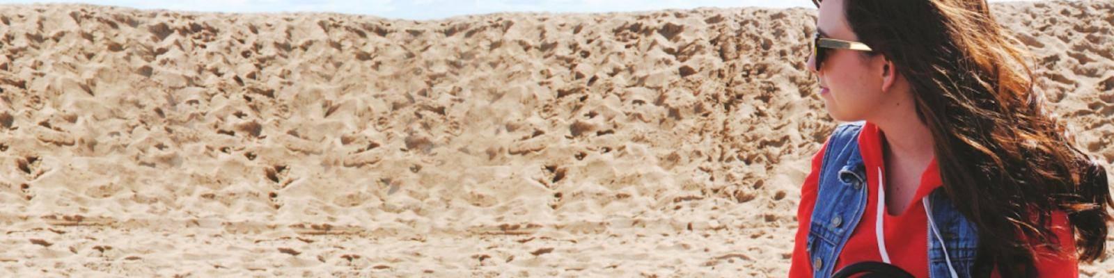 Meisje met zonnebril in zand