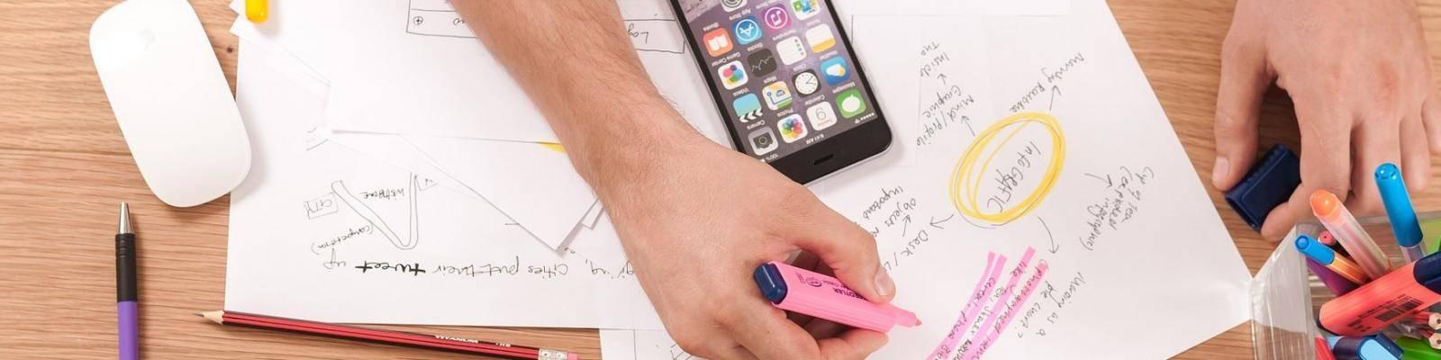 Handen met papierwerk, pennen en telefoon