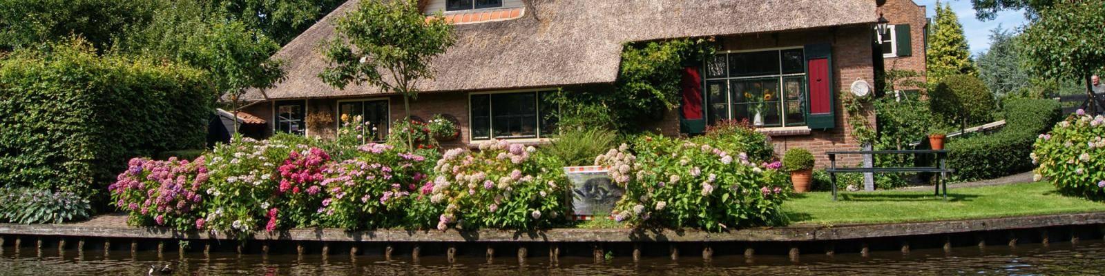 Huis met rieten dak aan water